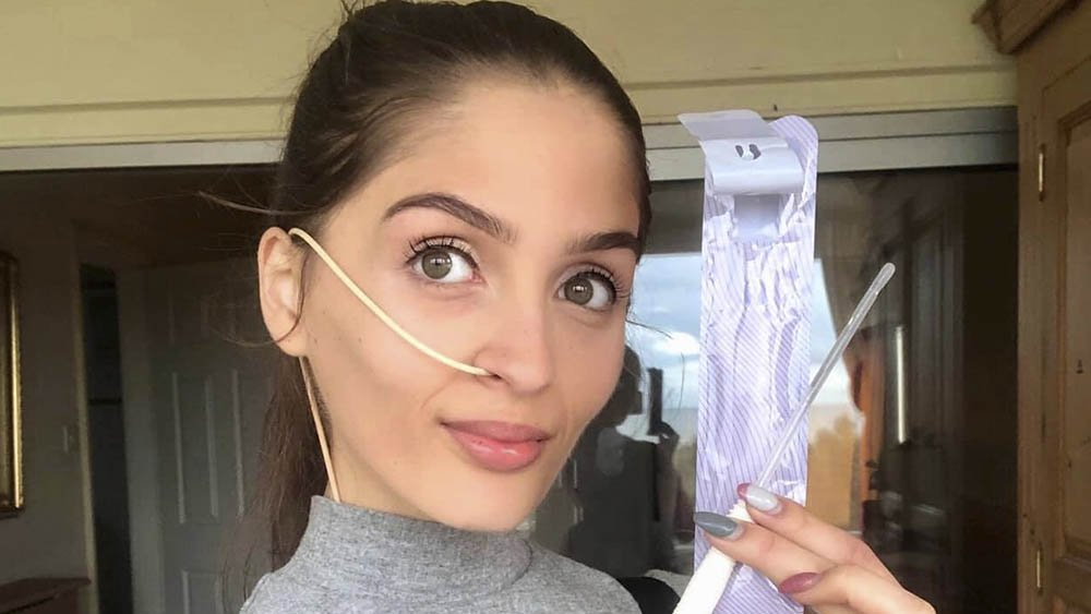 Evie confidently holding a catheter for managing her bladder and supporting her independence
